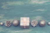 Slavnostní složení plochý ležel vánoční hračka míčky kužely vločky stříbrné krabice dřevěné vintage pozadí. Pohled shora kopie prostor