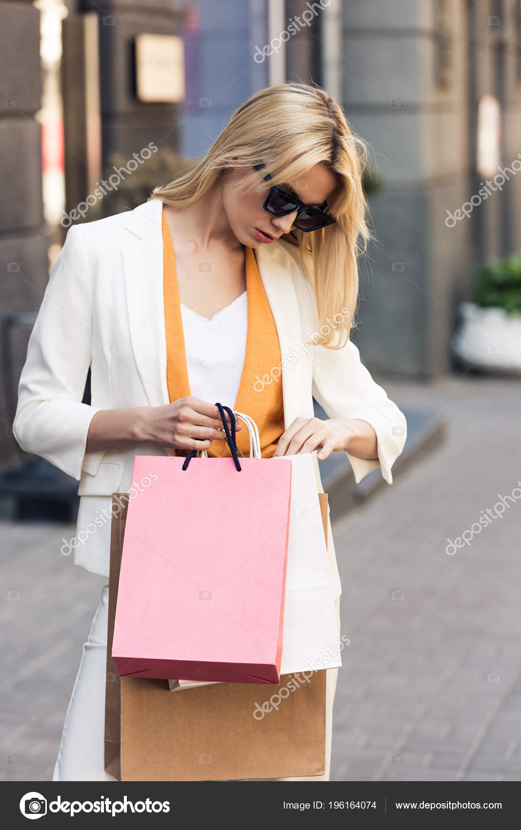 02d4f02ccf Κομψό Νεαρή Γυναίκα Γυαλιά Ηλίου Που Ψάχνει Τσάντες Για Ψώνια — Φωτογραφία  Αρχείου