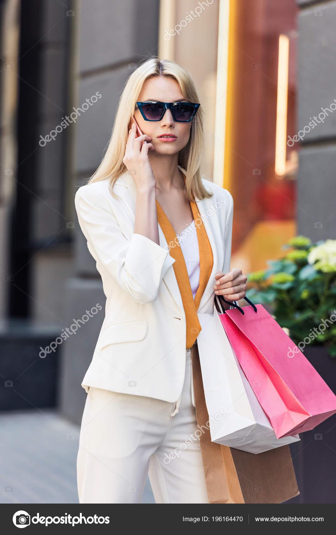 7ca903af2c Μοντέρνα Νεαρή Γυναίκα Γυαλιά Ηλίου Κρατώντας Χάρτινες Τσάντες Και Μιλάμε — Φωτογραφία  Αρχείου