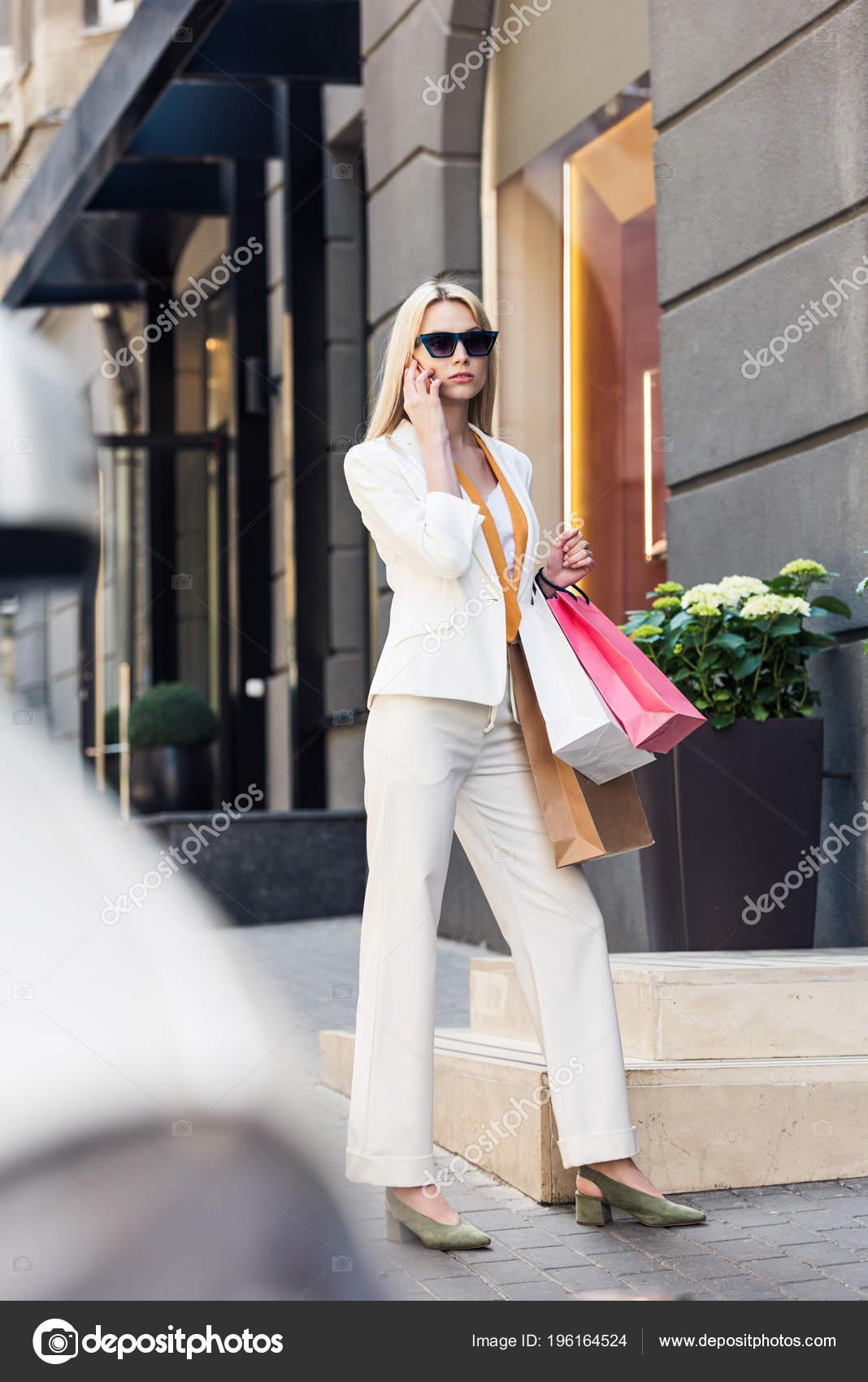 25d9c7cd0e Επιλεκτική εστίαση της μόδας νεαρή γυναίκα σε γυαλιά ηλίου κρατώντας  χάρτινες τσάντες και να μιλάμε από το smartphone στην οδό — Εικόνα από ...