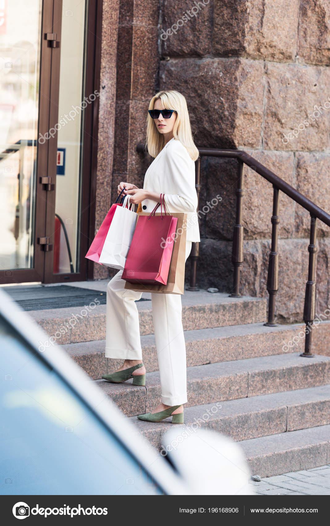 f83c117112 Όμορφη Μόδας Ξανθιά Γυναίκα Κρατώντας Τσάντες Για Ψώνια Και Στέκεται — Φωτογραφία  Αρχείου