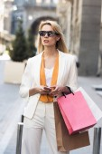 Fotografie beautiful young blonde woman in sunglasses holding smartphone and shopping bags on street