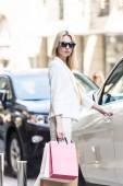 Fotografie elegantní mladá žena v brýle, nákupní tašky a otevírání aut