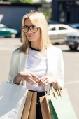 beautiful blonde woman in eyeglasses holding shopping bags and looking away on street