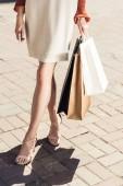 oříznuté záběr mladá žena držící nákupní tašky na ulici