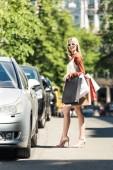 Fotografie voller Länge Blick auf stilvolle junge Frau mit Papiertüten stehen in der Nähe von Auto auf Straße