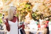 Stylový blond dívka držící papírové tašky a při pohledu na figuríny v butiku