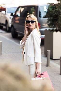 selective focus of young woman in sunglasses holding shopping bags and talking by smartphone on street