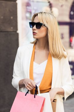 beautiful young woman in sunglasses holding paper bag and looking away on street