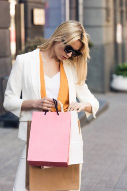 stylish young woman in sunglasses looking into shopping bags on street