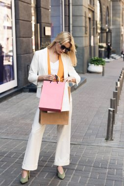 full length view of stylish young woman looking into shopping bags on street