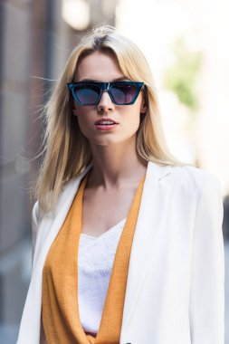 portrait of beautiful young blonde woman in sunglasses looking at camera