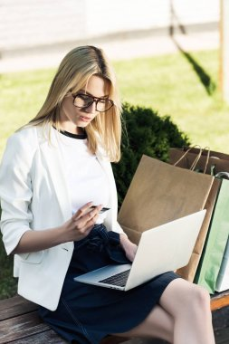 young woman holding credit card and using laptop while sitting on bench with shopping bags