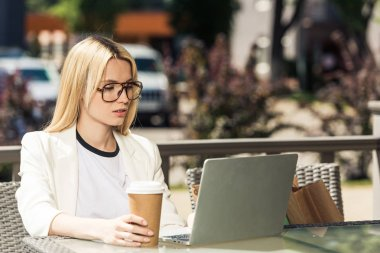 young blonde woman in eyeglasses holding disposable coffee cup and using laptop