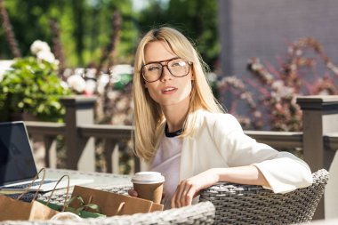 beautiful blonde girl in eyeglasses holding disposable coffee cup while using laptop