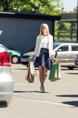 selective focus of stylish blonde girl with shopping bags walking on parking lot