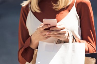 close-up partial view of young woman with paper bags using smartphone