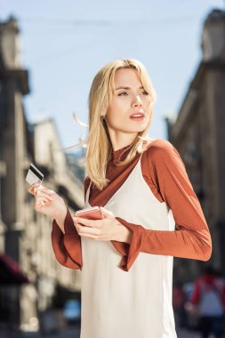 beautiful young blonde woman with smartphone and credit card looking away on street
