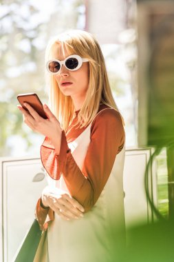 beautiful blonde girl in sunglasses holding paper bags and using smartphone