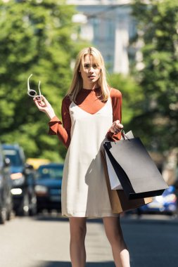 beautiful stylish blonde girl with sunglasss and shopping bags looking at camera on street