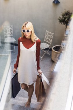 selective focus of beautiful stylish blonde girl holding paper bags on stairs