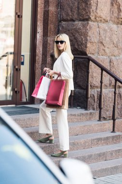 beautiful fashionable blonde woman holding shopping bags and standing on stairs