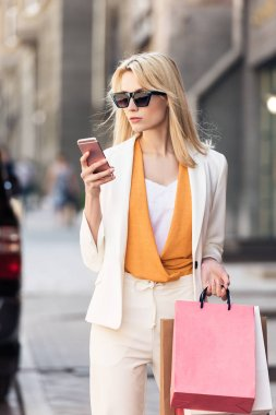 stylish blonde woman in sunglasses holding shopping bags and using smartphone on street