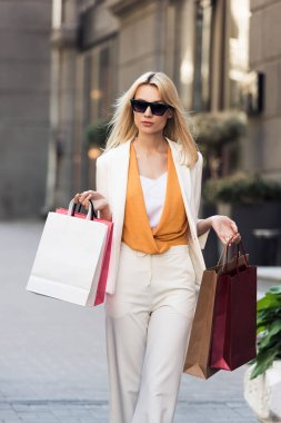 beautiful stylish blonde woman holding shopping bags and walking on street