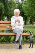 elderly woman in sportswear using smartphone while sitting on bench with sport bottle of water