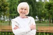 Lächelnde Seniorin mit verschränkten Armen im Park