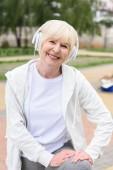 Fotografie smiling elderly woman listening music in headphones
