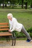 Seniorin mit Kopfhörer macht Liegestütze nahe Bank im Park