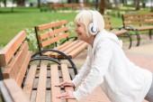 Fotografie Senior sportliche Frau in Kopfhörer training in der Nähe von Bänken im park