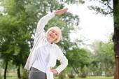 Ältere Frau in Sportkleidung trainiert und dehnt sich im Park