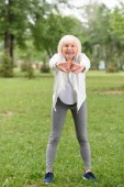 senior sportswoman stretching on green lawn in park