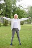 usměvavá vedoucí sportovkyně školení na zeleném trávníku v parku