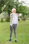 vedoucí kavkazské sportovkyně cvičení na zeleném trávníku v parku