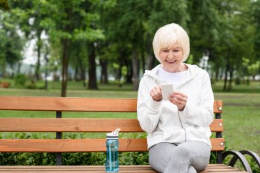 senior woman using smartphone while sitting on bench with sport bottle of water