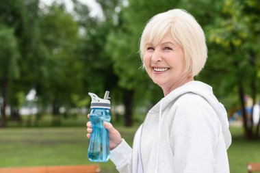 senior woman holding sport bottle and smiling at camera