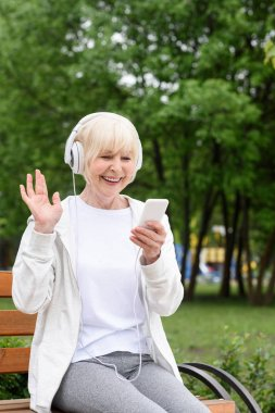cheerful elderly woman listening music with headphones and smartphone in park