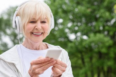 smiling senior woman using smartphone and headphones in park