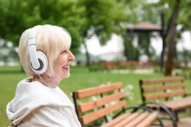 smiling senior woman listening music in headphones and sitting in park