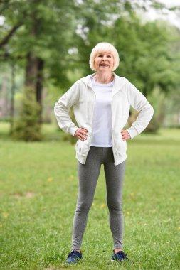 elderly sportswoman standing on green lawn in park