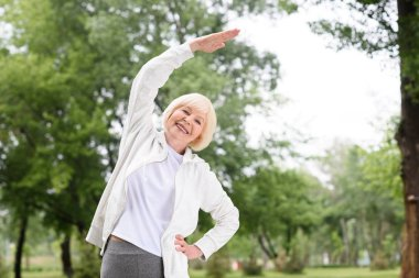 elderly woman in sportswear exercising and stretching in park