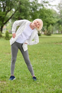 happy senior sportswoman exercising on green lawn in park
