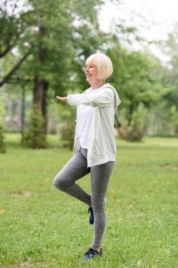smiling elderly sportswoman exercising on green grass in park