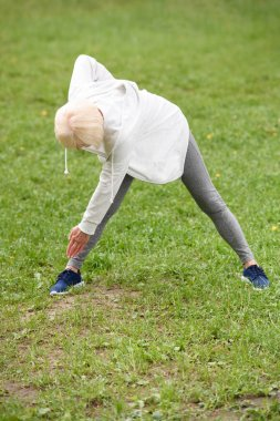 senior sportswoman stretching on green lawn in park, healthy lifestyle