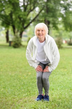 happy senior sportswoman squating on green lawn in park