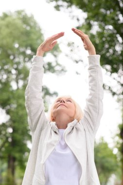senior athletic woman exercising and stretching in park
