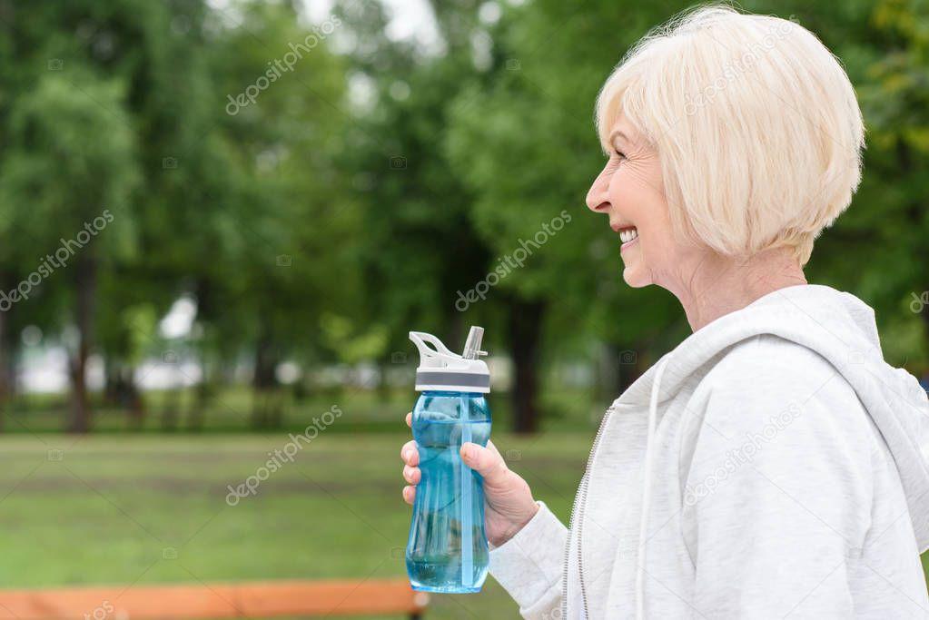 profile portrait of happy senior woman holding sport bottle